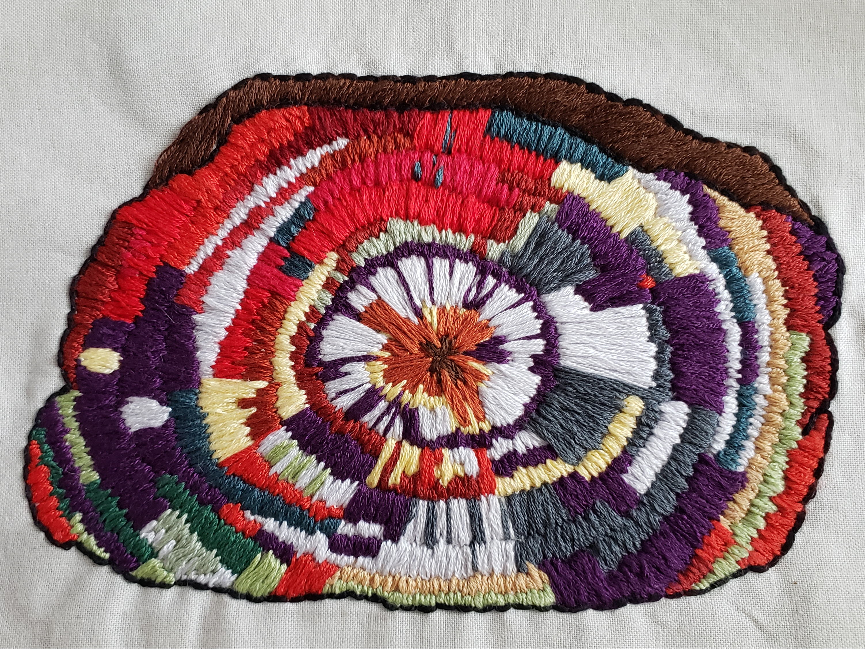 An embroidered interpretation of a cross section of a petrified tree trunk. Different coloured threads represent different minerals that grew within tree rings. Most prominent are reds, purples, and whites. The colourful piece sits on a white background.