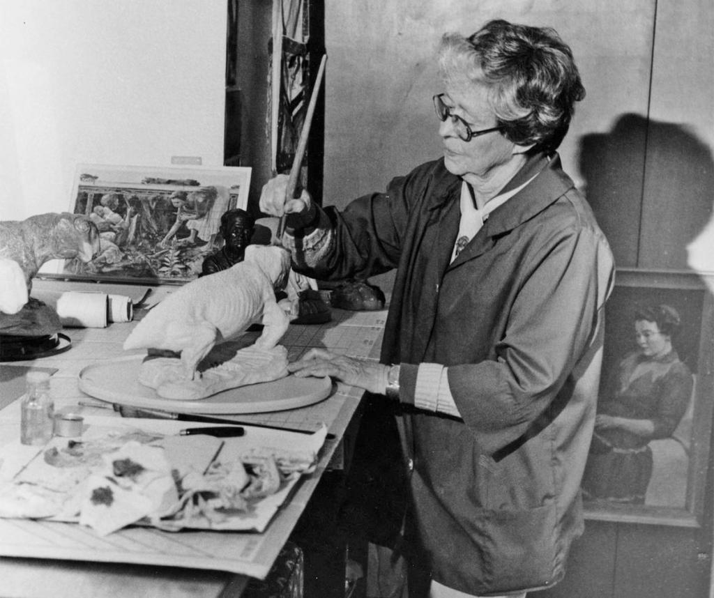 Black and white photograph of Margaret Matthew Colbert, an elderly white woman with short, wavy hair and thick-rimmed glasses. She's wearing a smock and standing at a workstation where she's sculpting one of the first Lystrosaurus models. Around her are painting and sculpting supplies, and a complete Lystrosaurus sculpture. On the floor leaning on the wall is a painting of a young woman, possibly Margaret or her mother.